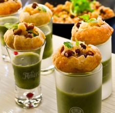 green-sauce-poured-into-shot-glasses-each-topped-with-fish-cakes-hour-derves-garnished-with-red-beans-and-parsley