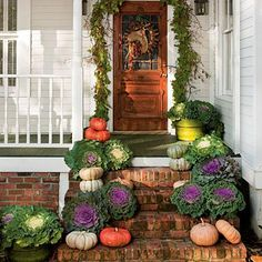 Pair pumpkins with potted kale to create a warm welcome. Grace an entry with a garland made of clippings from the garden. | SouthernLiving.com