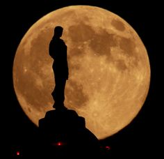 Image: A statue of agriculture goddess Ceres atop the state Capitol in Jefferson City, Mo., is silhouetted against a harvest moon. Credit: Charlie Riedel / Associated Press.