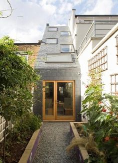 This is a 7.5 foot wide three-story terrace house located on the busy streets of St John's Hill, Clapham, London. It has a sloping roof with skylights for plenty of natural light to flow in to each room to create a spacious feel. The ground floor has a kitchen, dining area, and bathroom. On the second floor there is a bedroom and bathroom, and the third floor is a sleeping loft.  Narrow gravel backyard