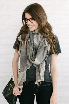 Neutral block scarf over graphic tee, neutral flats, dark denim.