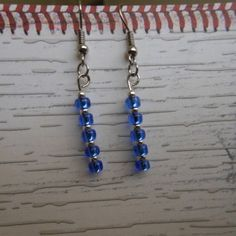 """Use the coupon code WEAREOPEN to save 10% on orders overs over $15 as a GRAND OPENING SPECIAL... Stainless steel hook earrings with clear blue glass """"E"""" beads and bright silver plated metal separator beads."""