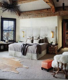 The rustic-glam touches along with the unexpected modern accents -- like the light fixture above, orange footstool and white lamp. I liked t...