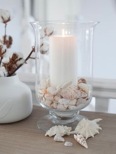 Crafted from hand-blown clear glass, our beautiful glass hurricane lamp is a stylish table accessory. Outdoor Candle Holders, Hurricane Candle Holders, Tropical Decor, Coastal Decor, Glass Hurricane Lamps, Seashell Crafts, Seashell Decorations, Vases Decor, Centerpieces