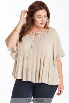 This passionate, free-flowing top features butterfly sleeves and a front tie with keyhole exposure. It finishes with tiers of ruffled hemlines along the bottom half for a classic feminine feel. Pair with your best skinny jeans and sandals for a day look or heels for a sweet evening out. This top is unlined.