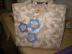Bolsa forrada em algodão100%, com enchimento de manta acrílica, com aplicações de flores em tecido contrastante e botão para fechamento.