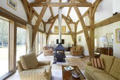 Fully vaulted sitting room with large feature sling brace truss. Two seating areas are created by the centrally positioned wood burning stove. Fully glazed southern wall overlooks garden and gives large amounts of light to the sitting area.