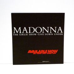 Madonna - Vintage Poster Flat 2 Sided Display - The Girlie Show - Live Down Under - 1994  Measures: 12 3/8 by 12 3/8 inches  This is a hard-to-find, promotional only flat  two sided record store display for Madonna from 1994 for her video and laserdisc release of her live performance.  Tags/marks/id: Maverick Recording Company 1994 Made in the USA Promotional only  Condition: Like New, never used  Our posters / record store displays are vintage originals, not reproductions. These promotional…