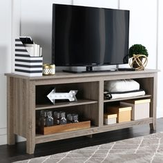 Stand up for better viewing of all your favorite soaps with this Driftwood 58-inch TV stand that fits right into a transitional or urban living room decor. The grey TV stand features multiple adjustab
