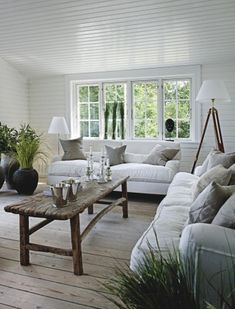 Natural living room-white painted wood, natural floor, over-stuffed white sofas and black pots!