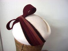 Filcový klobouček č.6349 Bílý filcový klobouček na gumičce ozdoben filcovými proužky v odstínech bordo a hnědé barvy. Hodí se na denní nošení, ke kabátu či kostýmu. Je velice slušivý a mladiství.