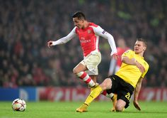 Alexis Sanchez of Arsenal is tackled by Lukasz Piszczek of Borussia Dortmund during the UEFA Champions League Group D match between Arsenal and Borussia Dortmund at the Emirates Stadium on November 26, 2014 in London, United Kingdom.