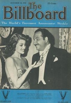 """Rita Hayworth admiring Grand Cross of Merit worn by Xavier Cugat. The decoration was conferred on Cugat by the Cuban government for popularizing Latin American music in the United States. Miss Hayworth co-stars with Fred Astaire, and Xavier Cugat and his orchestra are featured, in Columbia's new musical film """"You Were Never Lovelier."""""""