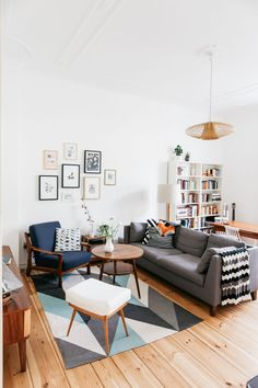 Mid-century modern living room with gray sofa, blue arm chair, and wood pendant lamp