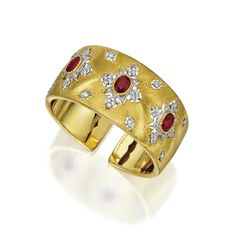 18 KARAT TWO-COLOR GOLD, RUBY AND DIAMOND BANGLE-BRACELET, BUCCELLATI The hinged cuff of satin-finished gold decorated with pierced floral motifs of modified lozenge shape, set with 3 oval rubies weighing approximately6.75 carats,further decorated with 68 small round diamonds, signed M. Buccellati.With signed box.