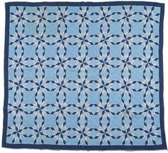 """Vintage Trapunto Star quilt, ca 1920's-30's. Cotton fabrics in prints and solids of multiple stars, all in hues of blue; having quilting of outline, squares and diamonds with alternating blocks and a border of trapunto leaves; 71"""" x 72"""""""
