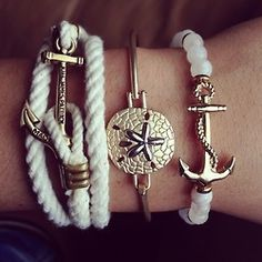 """Layered bracelets with a theme of the sea!  From left to right, you see a white """"rope"""" wrap with an anchor used as a toggle style closure, then in the center is a simple bangle featuring a sand dollar with starfish & at last, a pearl bracelet with an ornate anchor charm piece. All the antique gold metals compliment one another & clever elements like pearls from the sea & ropes from a sail boat bring the theme together & make it complete!"""
