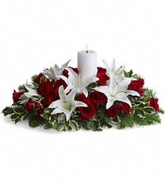 T128-3A Luminous Lilies. This luminous centerpiece is a glowing way to spread the joy of the season. Whether displayed on the dining table or placed elsewhere, it will light up any room with holiday cheer. Gorgeous pure white Asiatic lilies, radiant red roses, spray roses and pretty winter greens are arranged around an elegant white pillar candle. It's regal and radiant. H&J Florist and Greenhouses of St Joseph, MI 269-429-3621 would love to help you make your event special!