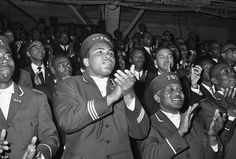 AboveMuhammad Ali applauds during a speech given by Elijah Muhammad at a convention of th...