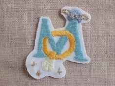 """白い木綿にアルファベットの""""M""""を手刺繍しました。図案は指輪と土星(Wリング!)のデザイン。刺繍部分のこんもりすべっとした肌触りが、かくれ... ハンドメイド、手作り、手仕事品の通販・販売・購入ならCreema。"""