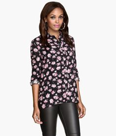 Embrace a darkly romantic vibe with this black long-sleeved shirt with roll-up tab, buttons, and floral print.│ H&M Divided