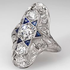 Edwardian North to South Dinner Ring Old Euro Diamond Sapphire Solid Platinum. This magnificent Edwardian North to South style dinner ring is crafted of solid platinum and features high quality old European cut diamond center stones and synthetic blue sapphires and genuine diamond accents. This ring is in very good condition and is 100 years old.