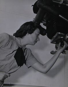 U.S. Navy WAVES Photographer's Mate Marjorie Sellers. She was one of two WAVES on photo duty at Naval Air Station Seattle. Here she's adjusting a lens on a photo lab enlarger.
