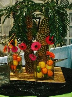 Beach theme party centerpieces... fruit in vase with gerber daises. For hawaian theme change to hawaii flowers