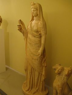 Persephone-Isis holds a seistrum and has a disc-and-crescent ornament on her head.  Archaeological Museum, Iraklion, Crete, Greece.