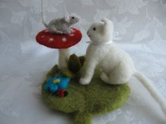 The needle felted cat is friends with the mouse on the mushroom
