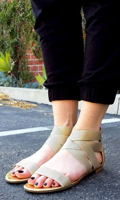 Elastic flat sandal with crisscrossing straps at the ankles and an open toe strap. Super easy to get into.