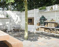 Buitenkamer verwerkt in schutting met haard, buitenkeuken, big green egg, buitendouche en openhaard.