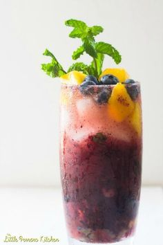 These blueberry mango mojitos are the epitome of summer! The colors are vibrant and the fruit sweet as a summer breeze. #mojito #blueberry #mango #drink #beverage #cocktail #recipe #party