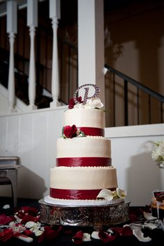 white wedding cake decorated with red ribbon & red roses
