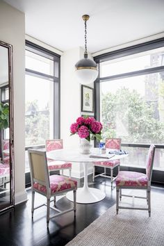 white tulip dining table with pink chairs