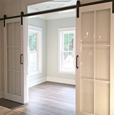 Sliding Glass Barn Doors - on barn door hardware - a great alternative to barn doors when the space lacks natural light - via Home Bunch