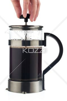 person lifting lid of coffee mug. - Close-up shot of a human hand lifting lid of a coffee mug against white background.