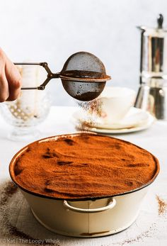 The dairy and gluten free tiramisu being dusted with cocoa powder, using an antique tea strainer. A cup of coffee, a cafetiere and more homemade gluten free ladyfingers are in the background.