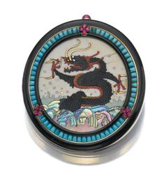 SUPERB GEM-SET COMPACT, CARTIER, 1920S – Sotheby's The circular compact with a water dragon motif composed of resin, ivory and mother-of-pearl, framed by black enamel, turquoise, and cabochon rubies, opening to reveal a powder compartment and a mirror