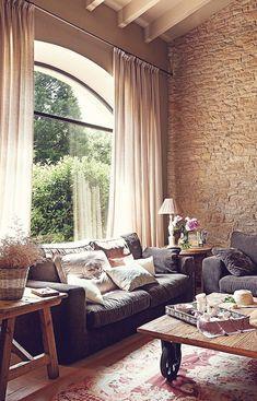 De novo as janelas bem grandes! Nesse ambiente ela foi essencial para trazer a iluminação natural ao cômodo. Gostei bastante porque a palavra para essa casa é aconchego: tijolos irregulares, madeira rústica e sofá fofinho cheio de almofadas! A cortina e o tapete ajudam a compor a sala.