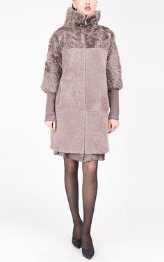 Модное многофункциональное пальто прямого силуэта из овчины и меха козлика с укороченным рукавом, съёмными трикотажными манжетами и отделкой натуральной кожей. Будет удачно сочетаться как с платьями, так и с одеждой в классическом и спортивном стилях. Воротник-стойка защитит от холодного ветра, а застежка-молния добавит практичности