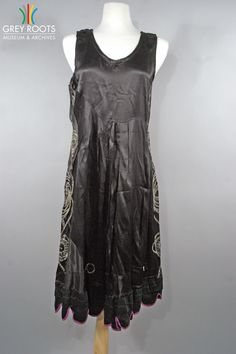 A black satin, sleeveless, flapper-era dress with a scalloped hem trimmed in purple. Grey Roots Museum & Archives Collection.