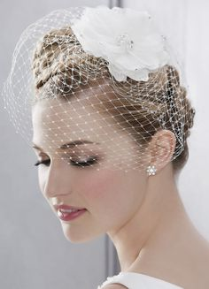A cute mini face veil set off with a sparkly flower! Charming when part of a vintage-inspired looks! (20122)