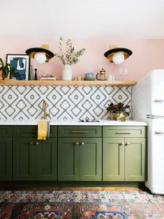 green kitchen cabinets with pink walls and black and white tile backs[lash