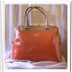 """Iacucci Italian Leather Handbag NWOT This unusual handbag is an Iacucci Pelletteria Italian leather handbag. Made in Italy. A structured frame measuring roughly 13"""" X 10"""". It has two short handles, inside zippered pocket and two smaller open pockets. It's tan and burnt orange with gold-tone detailing. NWOT. Comes with original dust bag. Iacucci Bags"""