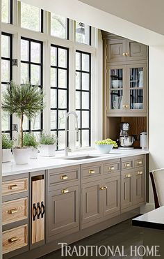black framed windows, light grey or taupe cab, white stone countertop, brass hardware