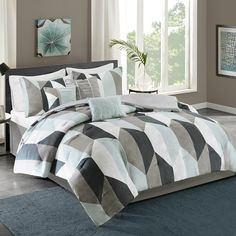 Make a statement with the Ashbourne 7 Piece Comforter Set by Home Essence.  The comforter features hexagons in two tone combinations using shades of blue, grey, and white for a bold, modern look.  Two matching shams and three decorative pillows complete the set.  Bedskirt included.