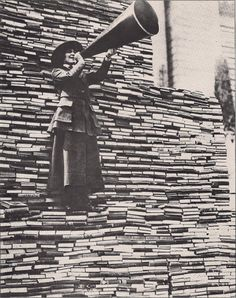 For the love of books:  Standing on a mountain of already donated volumes, an amiable barker calls for still more books from passers-by outside the New York Public Library on Fifth Avenue.    1910s, photographer unknown
