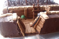100% edible World War One trench chocolate birthday cake. Raspberry jam and chocolate buttercream filling. Covered with chocolate buttercream. Details in gumpaste. Barbed wire is flash frozen chocolate sprayed with edible silver.