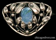 Forest Craft Guild brooch, , with leaves attached to wirework stems inside a triangular frame centering an oval bezel-set iridescent blue-green glass cabochon stone.  Possibly silver.